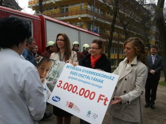 Az adományt jelképező csekket adja át a Kórház dolgozóinak (balról jobbra) Sándor Judit, kováts Adél és Jaksa Petra. Háttérben Rozgonyi Zoltán alpolgármester és a Zuglói Önkéntes Tűzoltók.