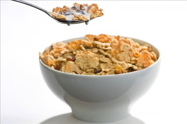 bowl of cereal with raisins and milk isolated
