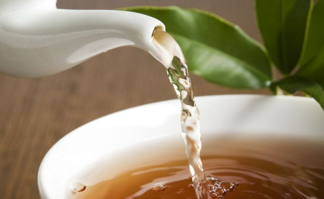 Cup of green tea pouring close up shoot
